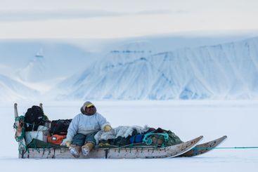 Dog sledding on frozen sea in front of mountain range.