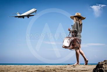 Woman with vintage leather travel bag on the beach