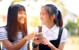 two asian teenager laughing with happiness face reading...