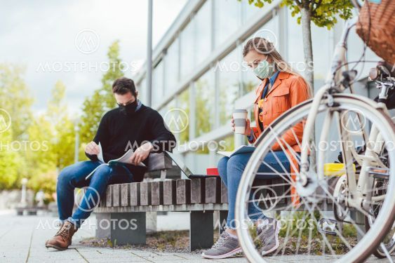 Two college students learning while keeping social distance
