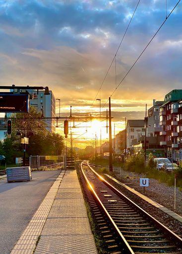 Människor på perrong i solnedgången väntar på tåg.