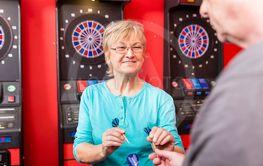 Mature woman holding dartboard arrows