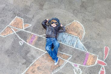 Little boy having fun with airplane picture drawing with...