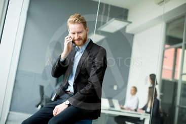 Businessman with ginger hair using mobile phone while...