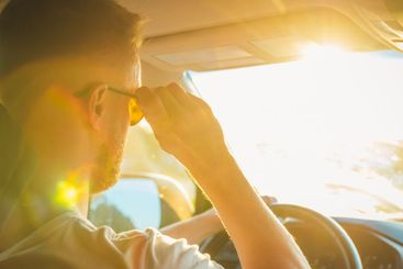 A man sits behind the wheel of his car on a sunny day