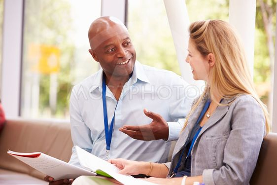 Two College Tutors Having Discussion Together