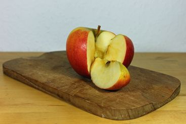 Two pieces cut out of an red apple on a wooden board...