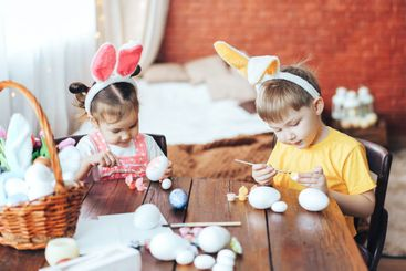 A boy and a girl are painting Easter eggs for the...