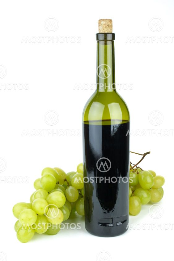 Flaske med røde vin og grønne druer nær