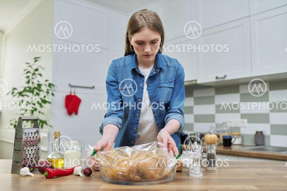 Young woman cooking baked chicken in baking sleeve with...