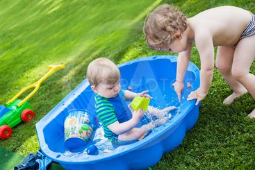 Two sibling boys having fun with water in summer