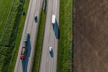 Transportation trucks and other vehicles on a highway in...
