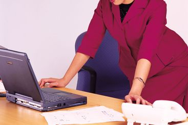 Businesswoman standing on the table with laptop