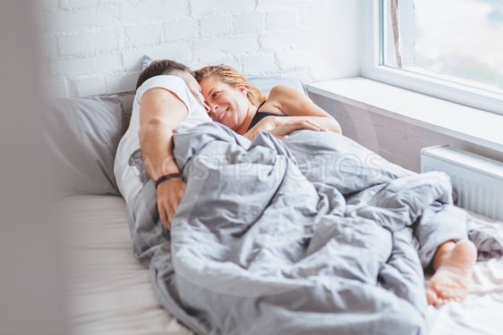 Young couple enjoying bed time in the morning