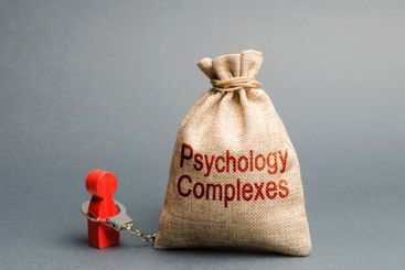 A person is handcuffed with a bag labeled psychological...