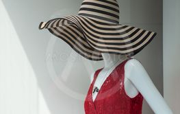 big summer hat and red dress on mannequin  in...