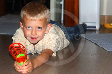 The little boy lies on a floor with a toy