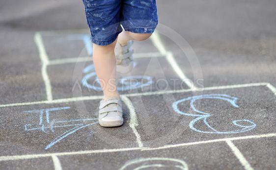 Closeup of little boy's legs and hopscotch drawn on asphalt