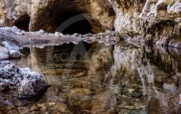 Cave entrance reflected in a clear river