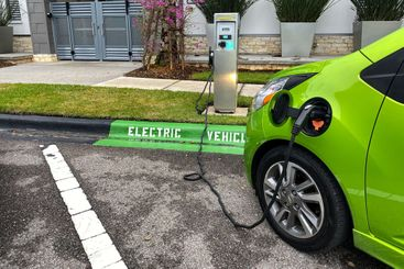 A lime green electric vehicle charging at a free public...