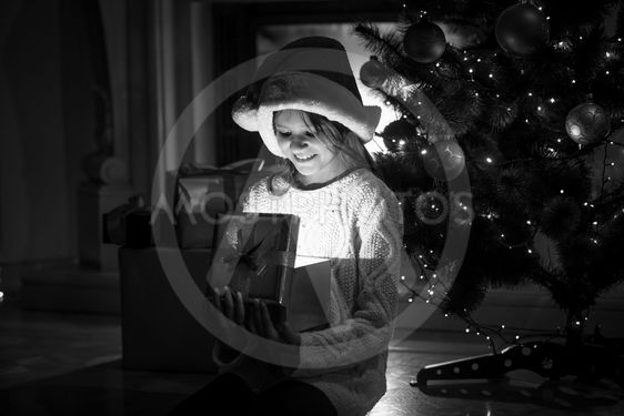 smiling girl looking inside of glowing gift box at...