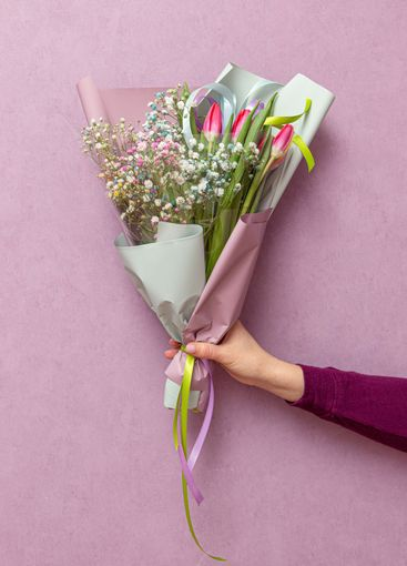 bouquet of Gypsophila Light Rainbow and tulips in a package