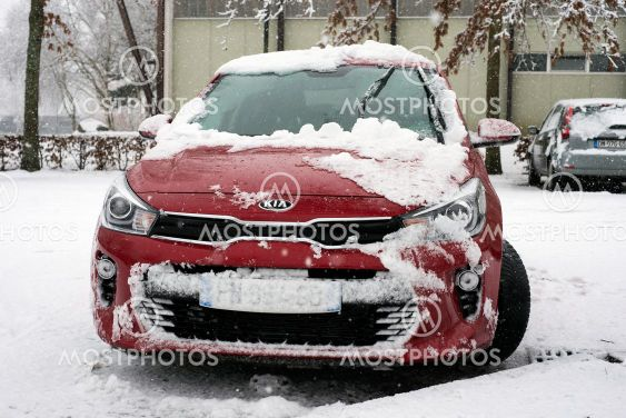 Front view of red KIA car covered by the snow parked in...