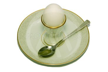 Eggcup with the egg and spoon on the plate