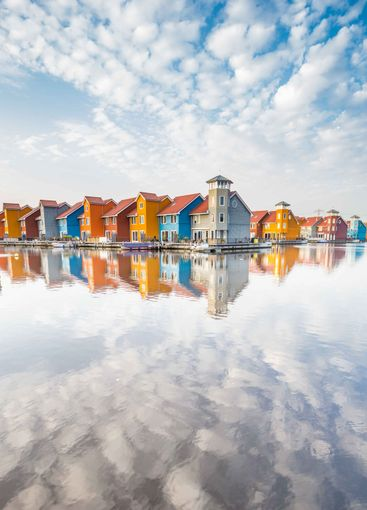 Colorful houses reflected in the water in Groningen in...
