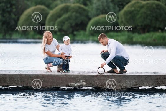 happy parents with their little son standing on the pier.