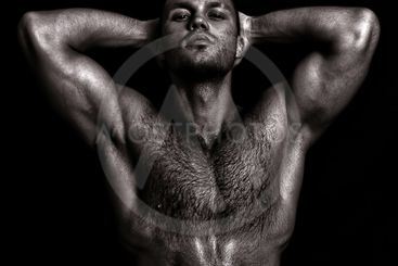 Nude muscular guy posing with hands behind head. Black...