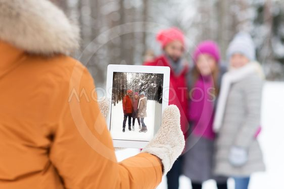 happy friends with tablet pc in winter forest