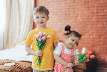 Boy and girl holding bouquets with tulips in their...
