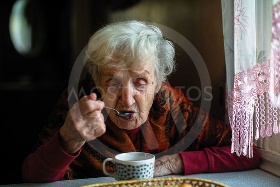 An elderly retired woman drinking tea from a spoon,...