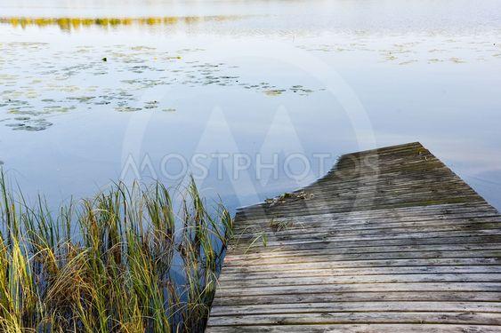 Gammal träbrygga som sjunker ner i sjön
