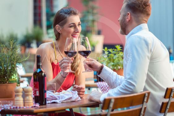 Young couple having red wine at restaurant