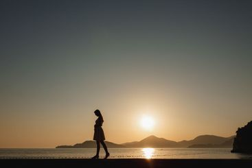 A pregnant woman walks on the seashore at sunset and...