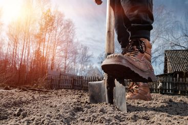 Boots and shovel closeup. The concept of the garden, the...