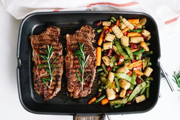Grilled beef steak with vegetables and rosemary in black...