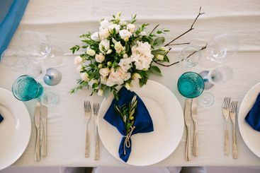 Wedding dinner table reception. White plates with blue...