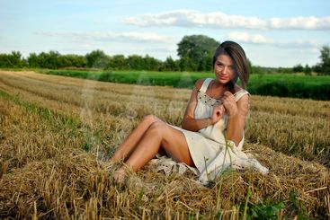 nice girl in national dress sitting on a field in rural...