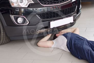 Young mechanic under car in service center.
