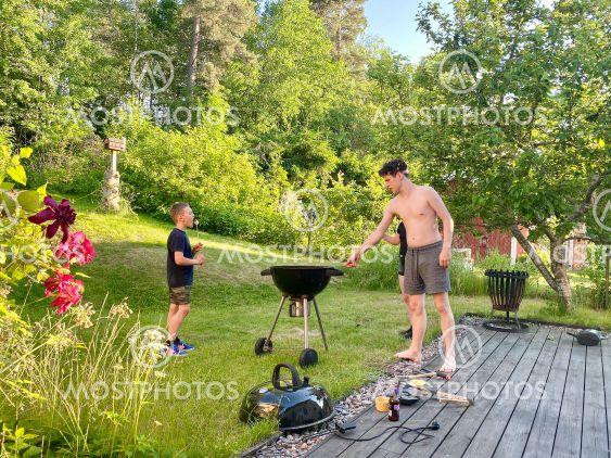 Barn och ungdomar grillar marshmallows i trädgården hemma.