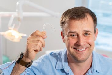 A smiling dentist doctor holds transparent aligners in...