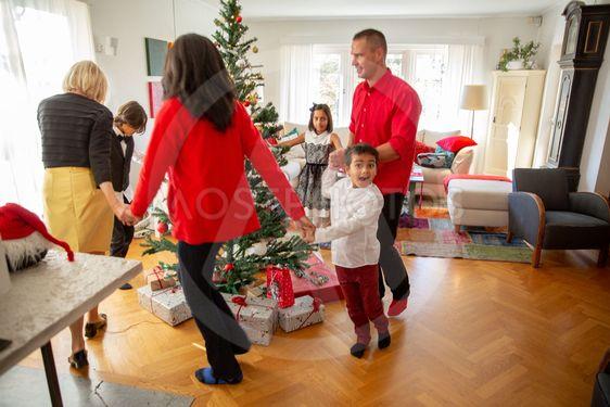 Familj dansar runt granen