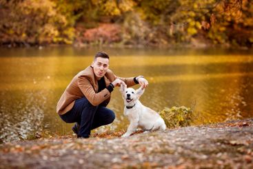 man walking with dog in autumn Park by river.