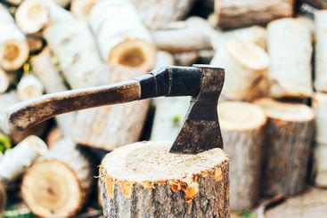 A sharp blade of an ax that sticks out in a wooden...