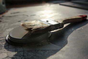 Brush placed on lid of a can on the floor to dry