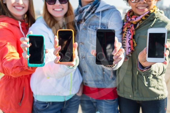 close up of friends showing smartphone screens