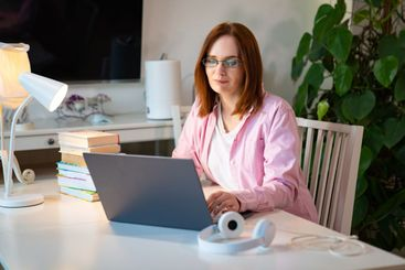 woman with dark hair in pink shirt study at home